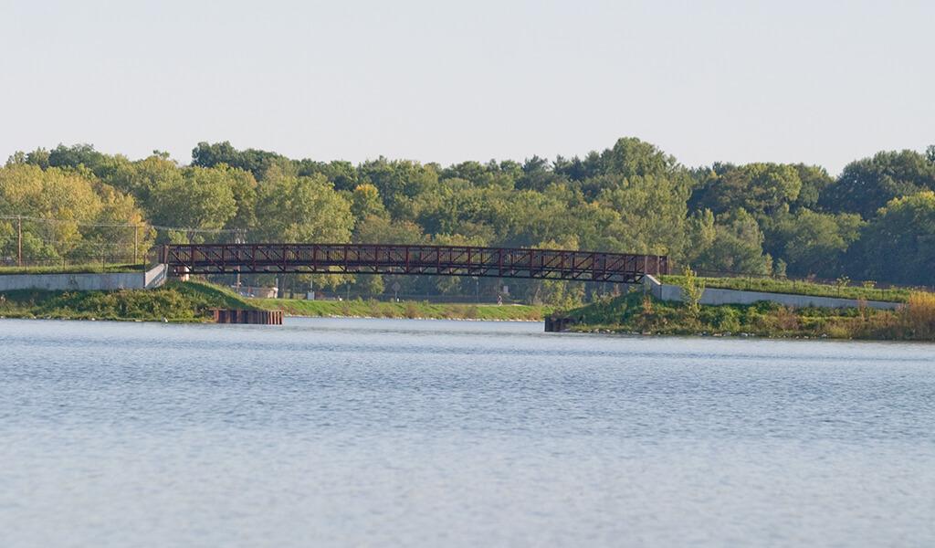 landscape view of the ada hayden pedestrian bridge from across the lake