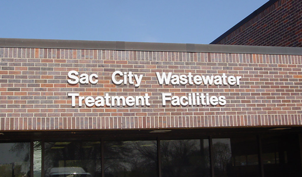 brick building with sign reading sac city wastewater treatment facility