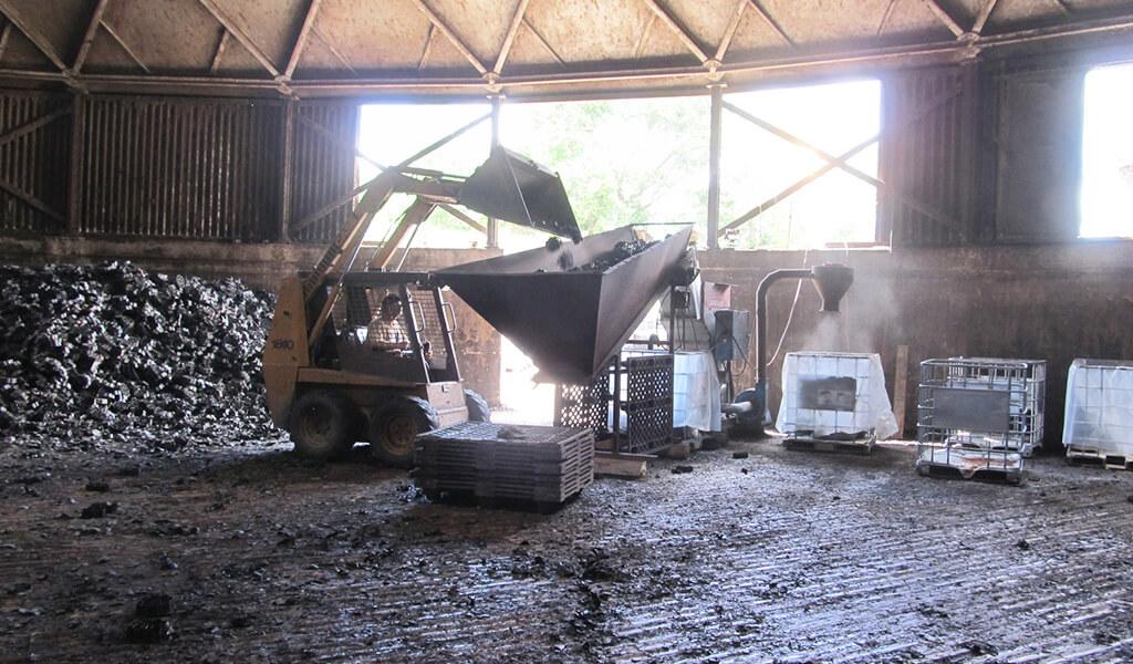 construction machinery dumps plastic into grinder