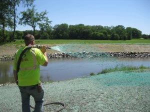 man spraying blue binder on soils