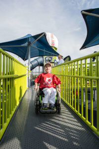 young boy in wheelchair playing on playground
