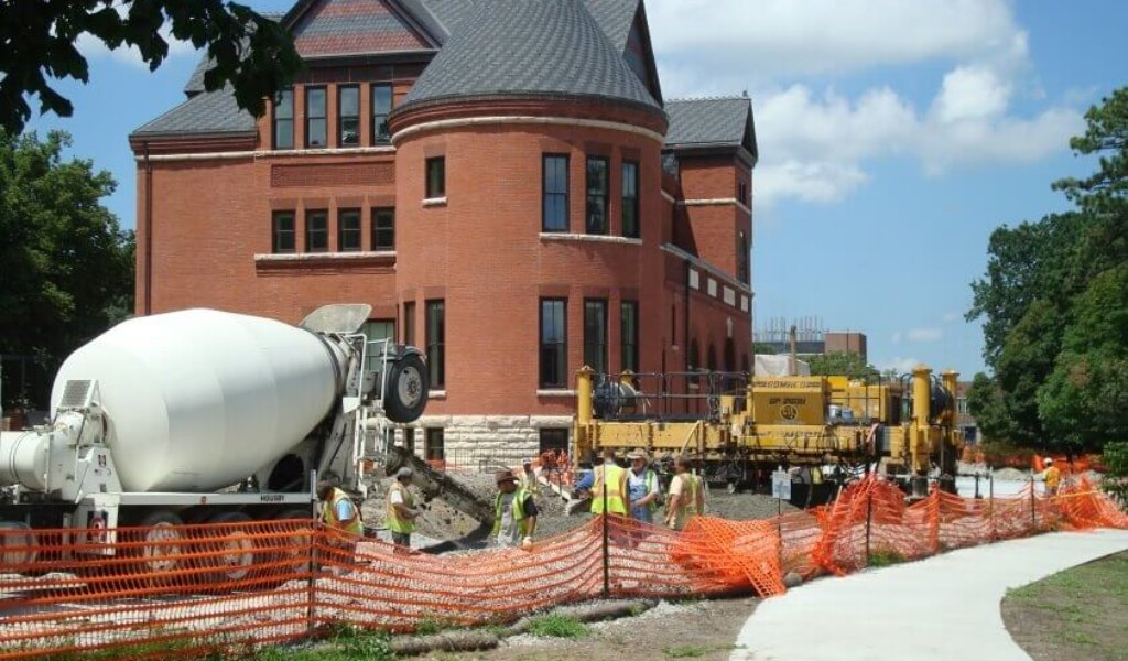Cement truck and construction workers pouring concrete in front of Morrill Hall on Iowa State University campus.