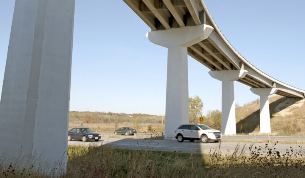 Tall interchange bridge over interstate with vehicles travelling underneath.