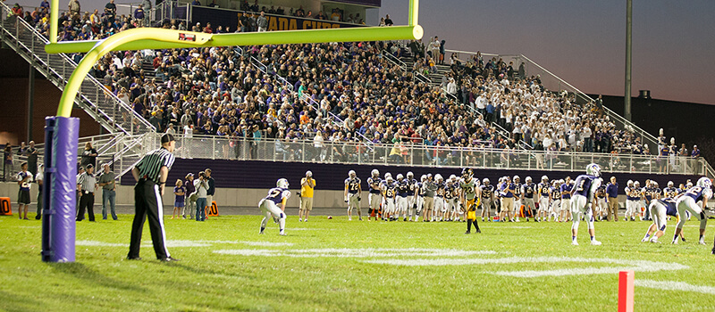 Fans watch as high school football game is going on.