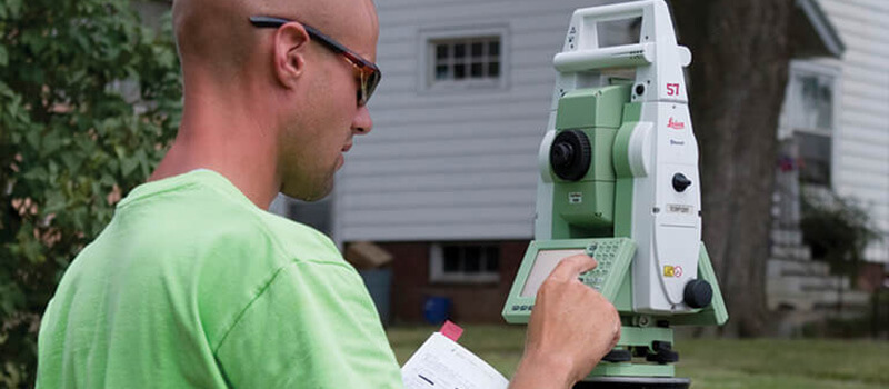 Up close of a man using survey equipment in the field.