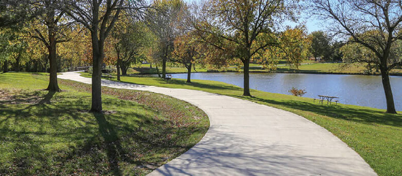 Winding paved trail along a lake.
