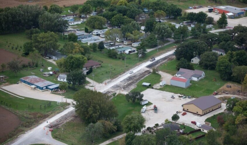 Aerial view of traffic moving through a construction zone with numerous homes and businesses along the roadway.