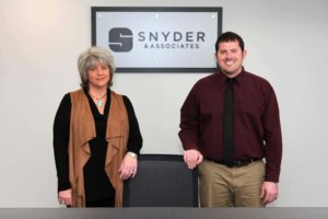 two snyder employees standing in front of sign at new office location