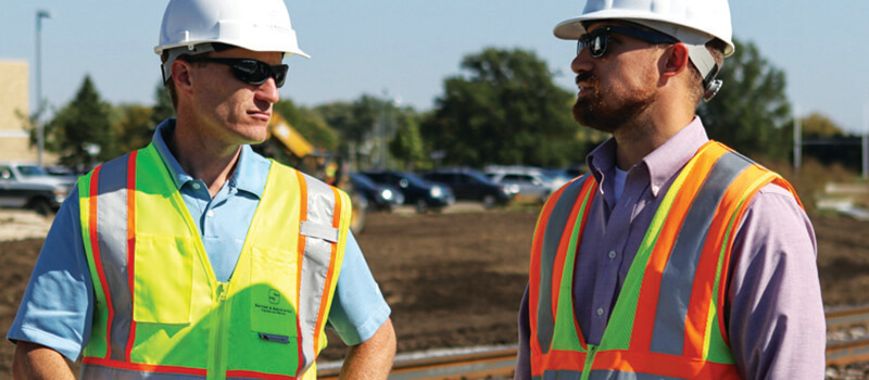 Two engineers discussing construction checks on site.