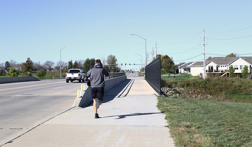 Man running on a pedestrian bridge