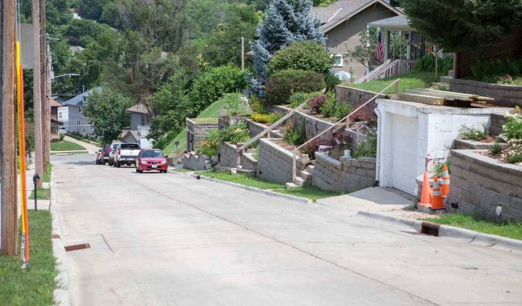Steep-grade city street with new retaining walls, resident access staircases, and stormwater drainage system.