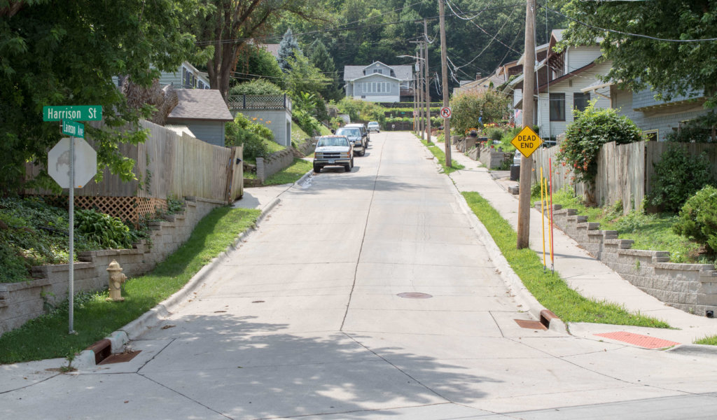 Newly paved residential city street on steep grade with new retaining walls.