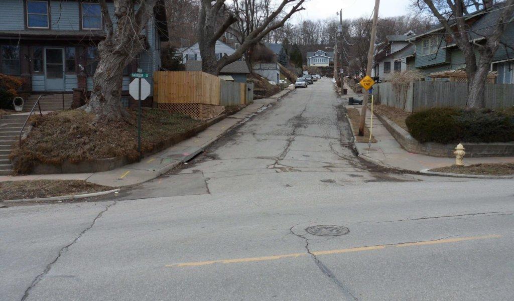A badly deteriorated neighborhood street and sidewalks with steep grade.
