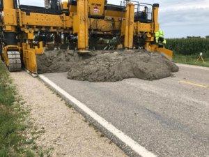 machine lays wet concrete over roadway