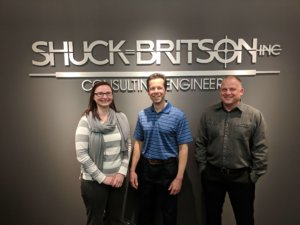 three employees in front of shuck britson sign
