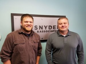two men in front of snyder sign