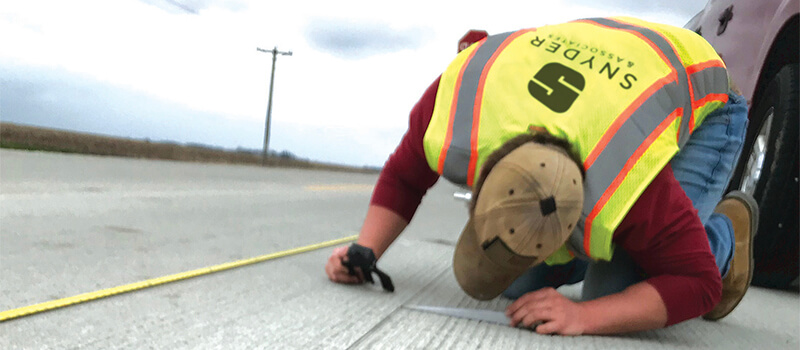 A man wearing a safety vest kneeling on pavement evaluating pavement with tools. .