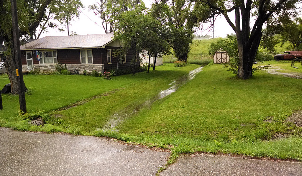 a stream of stormwater flooding running through a residential yard