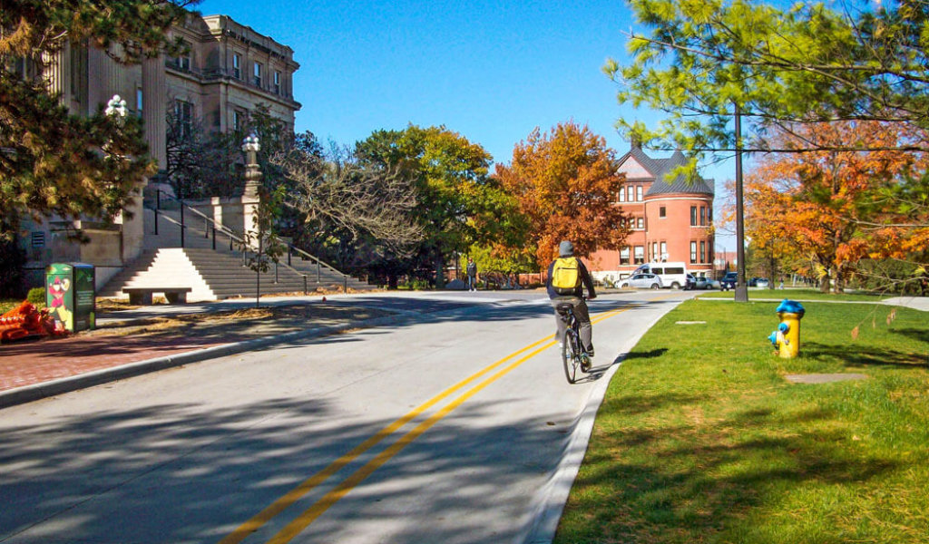 Bicyclist riding in bike lane in front of Beardshear Hall on Iowa State University campus.