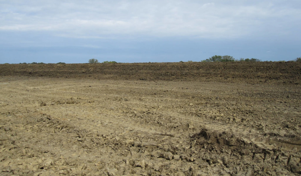 A photo of a clay liner nearing completion for a controlled discharge lagoon.