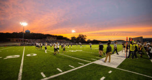 A sun sets over a high school football game.