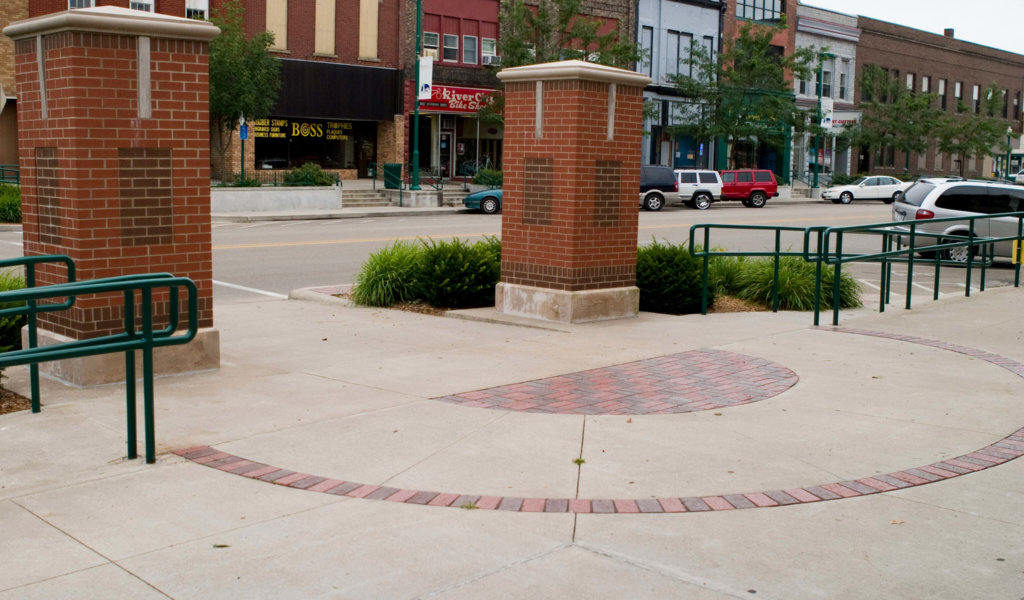 An image of large brick pillars, which are used to calm traffic and draw attention to pedestrian crosswalks for improved traffic safety.