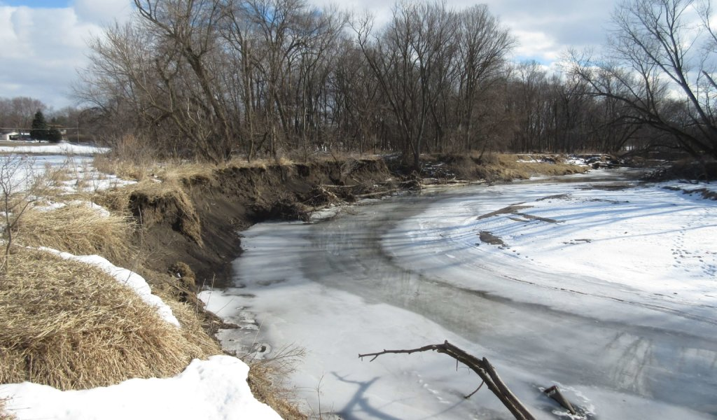 Accelerated bank erosion threatening sanitary sewer infrastructure in Four Mile Creek.