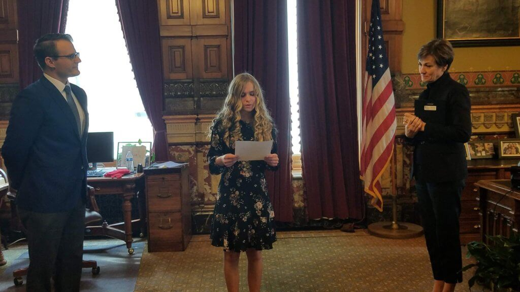 Larae Steiner, the statewide scholarship winner of the 2018 Iowa League of Cities If I Were Mayor Essay Contest, reads her essay to Lt. Governor Adam Gregg and Governor Kim Reynolds during an awards ceremony at the Iowa State Capitol.