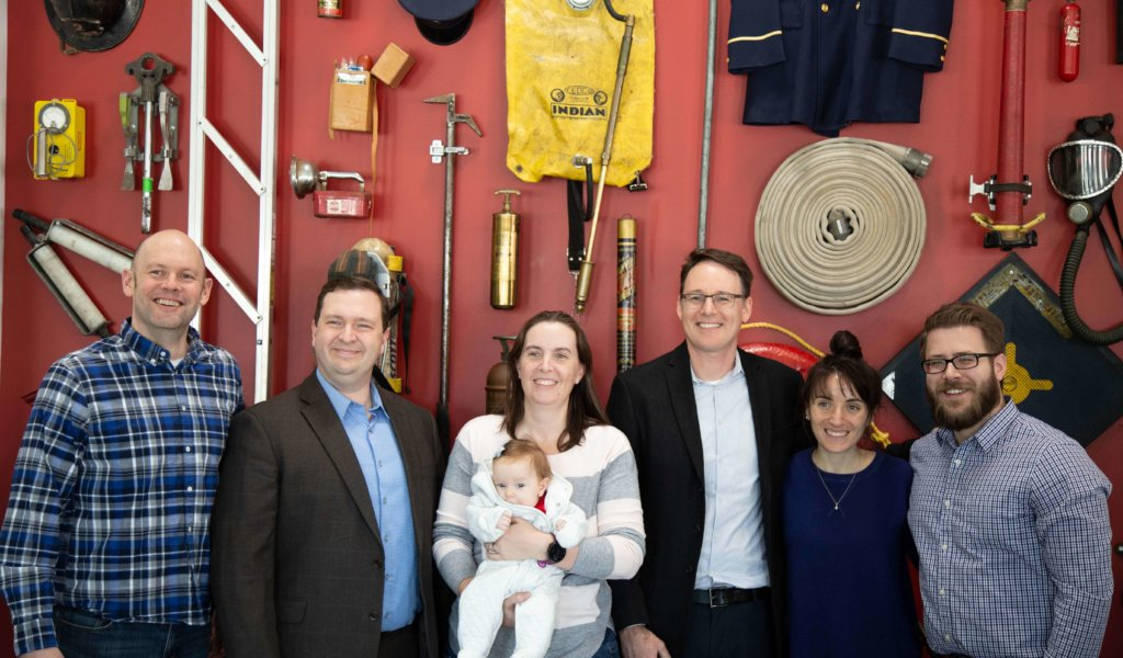 Design team stands in-front of red wall decorated with fire fighter items