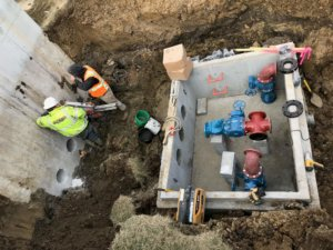 Construction workers drill holes into a SBR effluent flow equalization tank in order to install pump discharge piping that will carry wastewater effluent to a local ethanol plant.