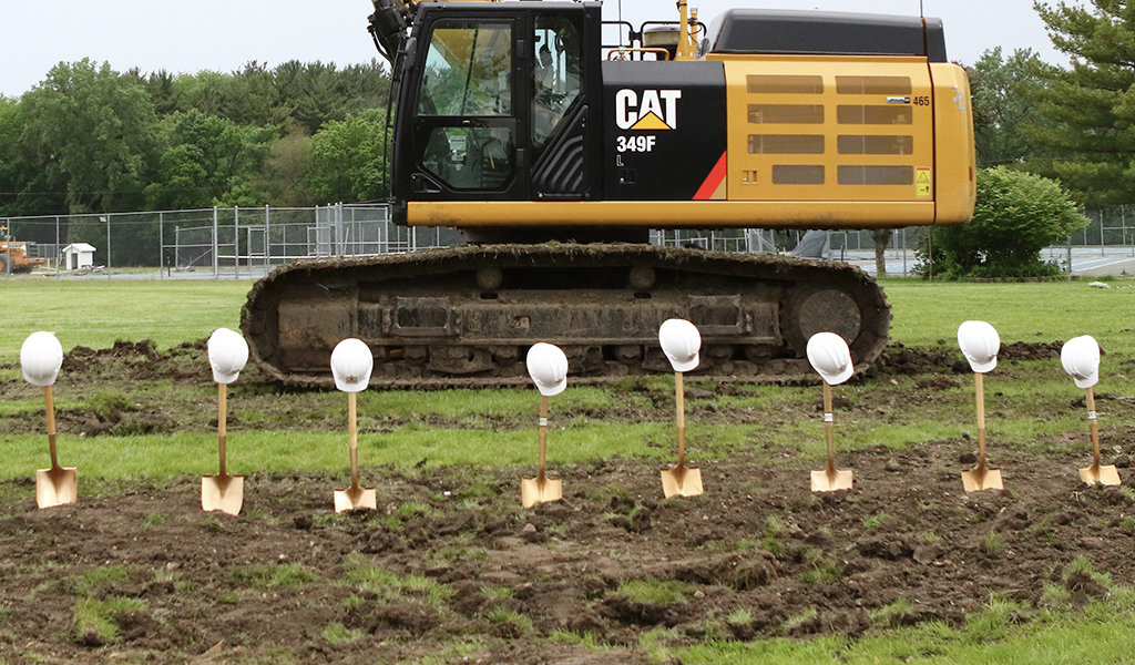 Eight gold shovels sticking out of the ground with a white hard hat on the handle in front of an excavato