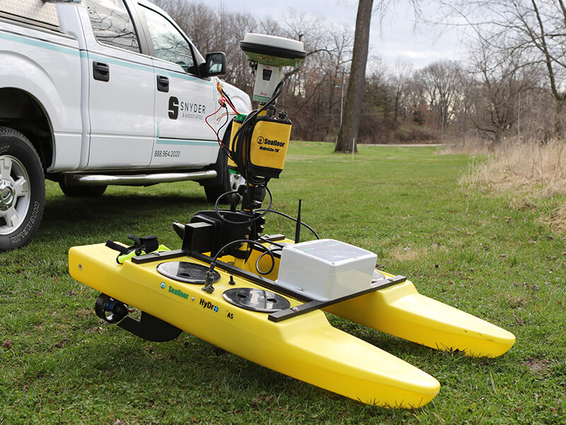 Yellow HyDrone sitting on the ground next to a Snyder & Associates land survey truck.