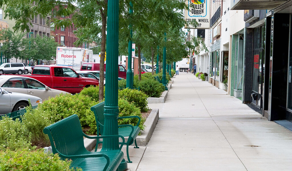 The downtown Clinton, Iowa streetscape uses planting beds, decorative lighting, and seating to create an inviting public space for pedestrians.