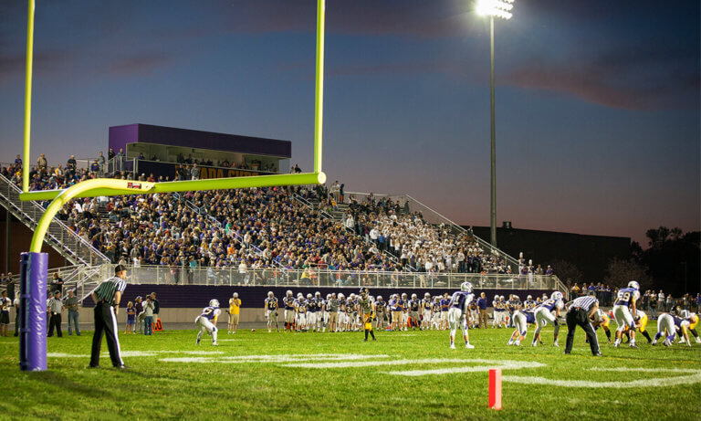 Football game at night, on the field behind goal post.