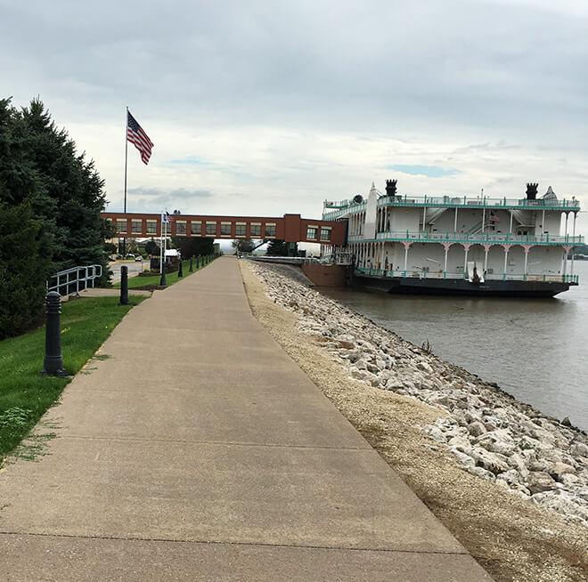 Riverboat floating along river shoreline