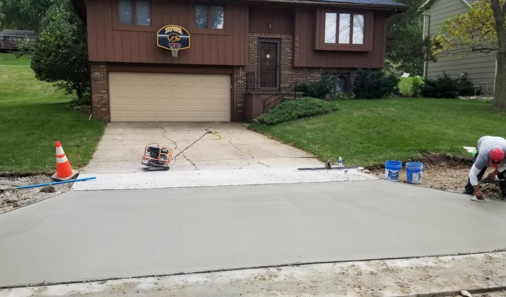 A worker smooths concrete on a freshly poured driveway apron.
