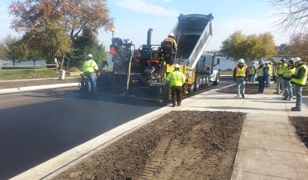 Hot mix asphalt being installed on residential street. Numerous crew and contractors on sight.