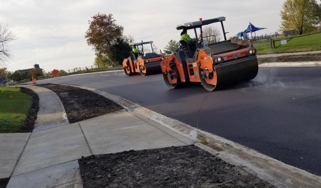Two large roller/compactors drive over fresh hot mix asphalt.