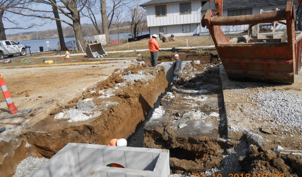 Storm sewer intakes and pipes between installed across a street.
