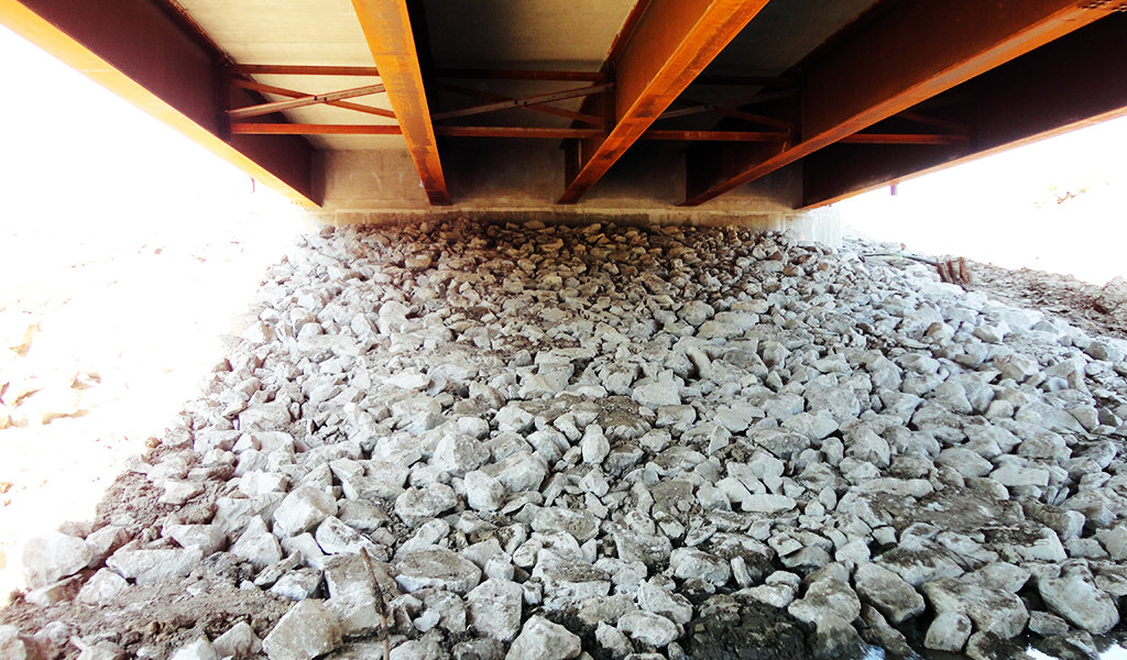 Large rocks piled below metal bridge as erosion control