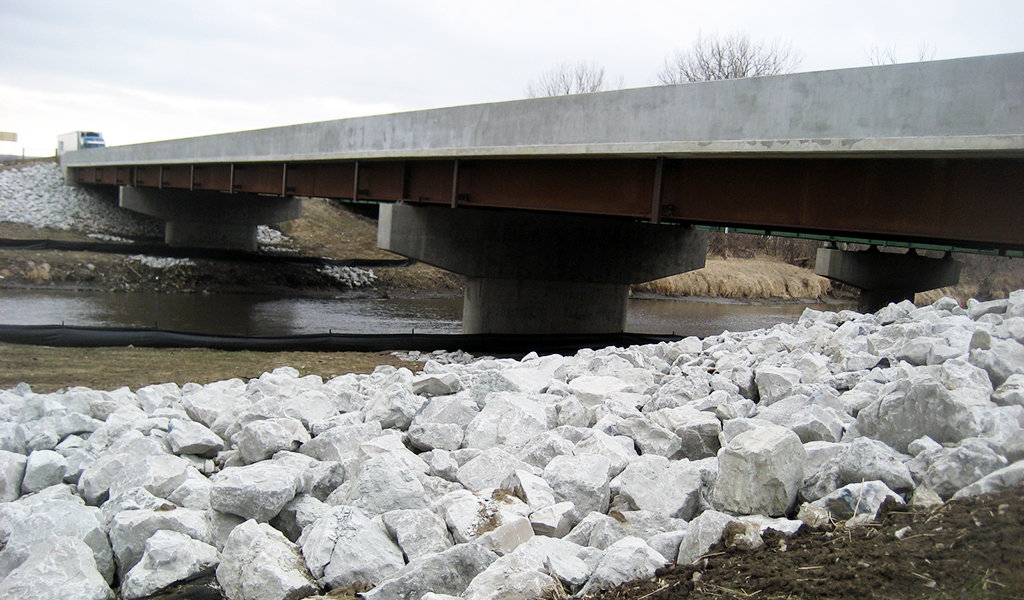 Completed bridge over river with erosion control rock along the banks