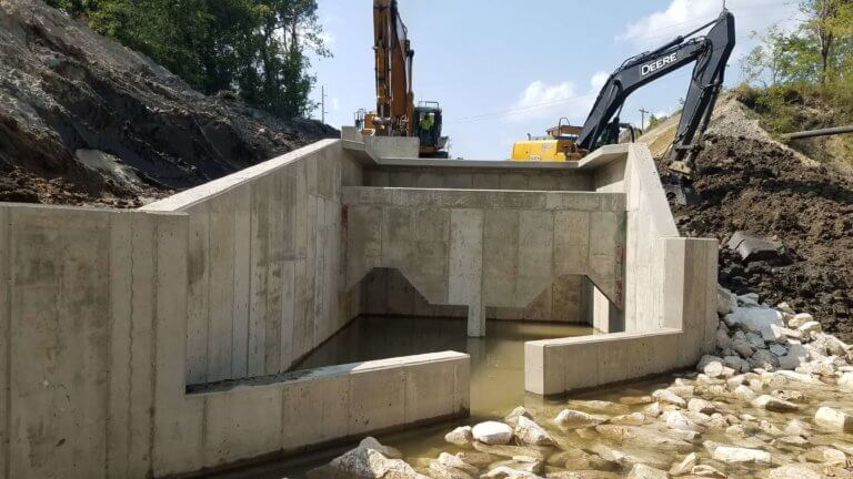 large concrete stormwater outlet structure with construction machinery behind it