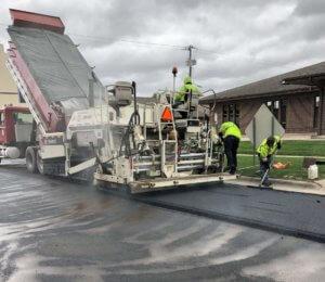 construction crews follow truck and machine laying asphalt