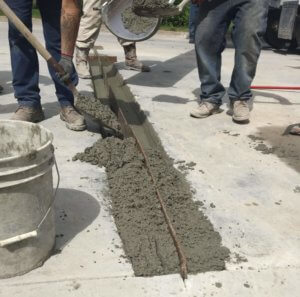 two men shovel wet concrete into place