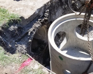 round pipe with connection holes being lowered into the ground