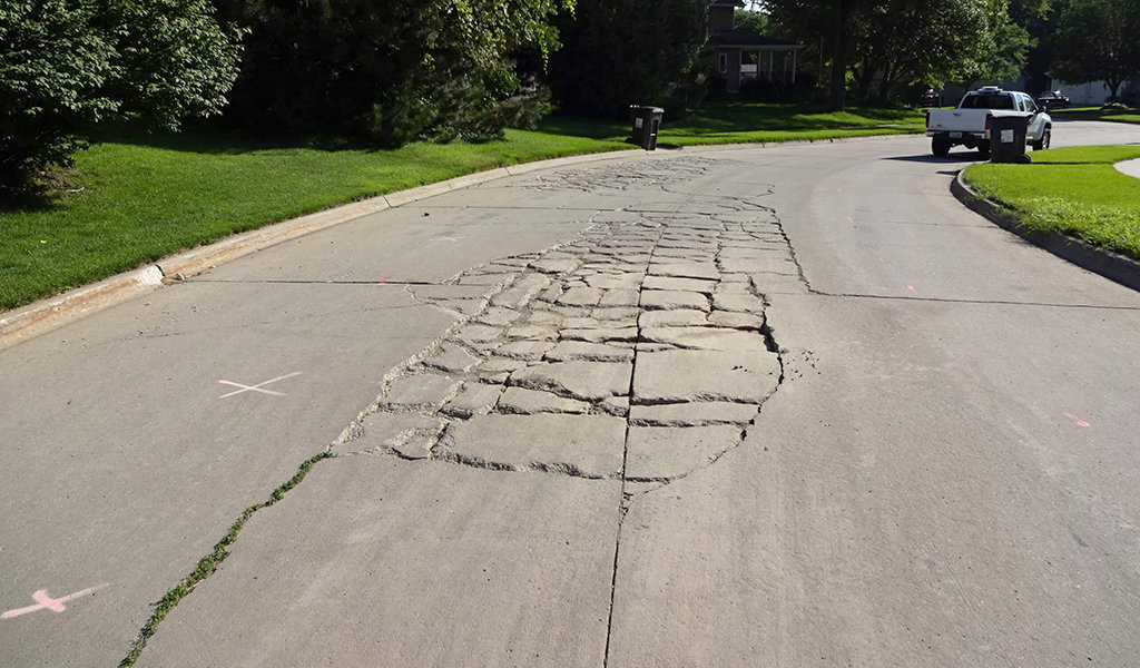 concrete roadway with shattered concrete in middle of drive