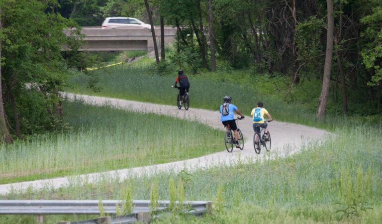 Pedestrians biking on a trail