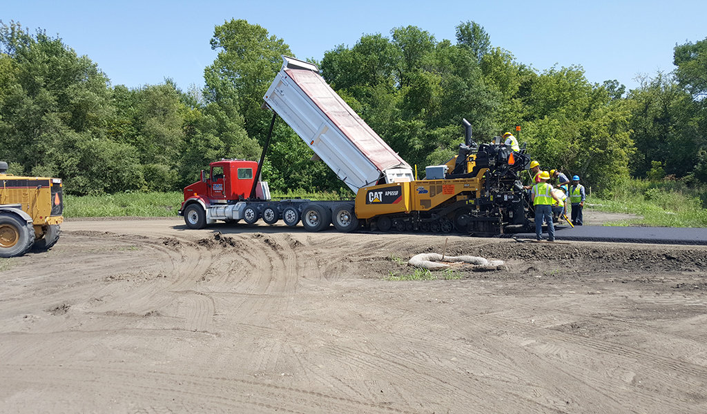 construction workers laying asphalt along the trail