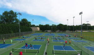 dozens of people mid-game on pickle ball courts
