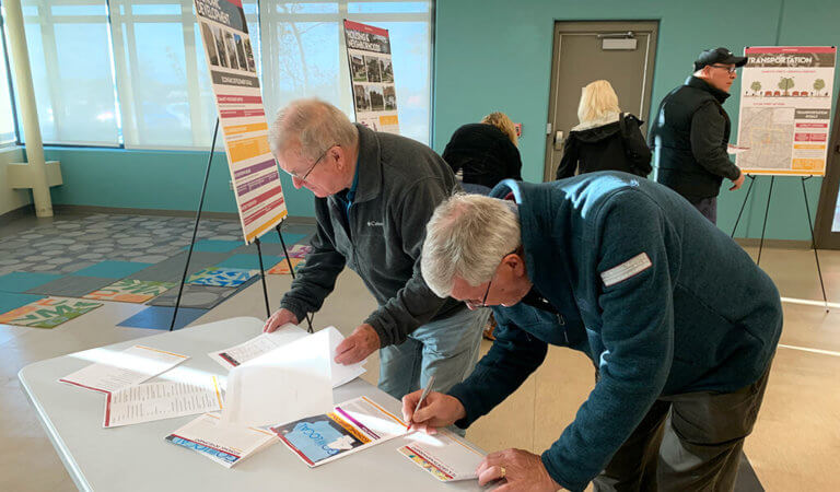 two men signing papers at an open house